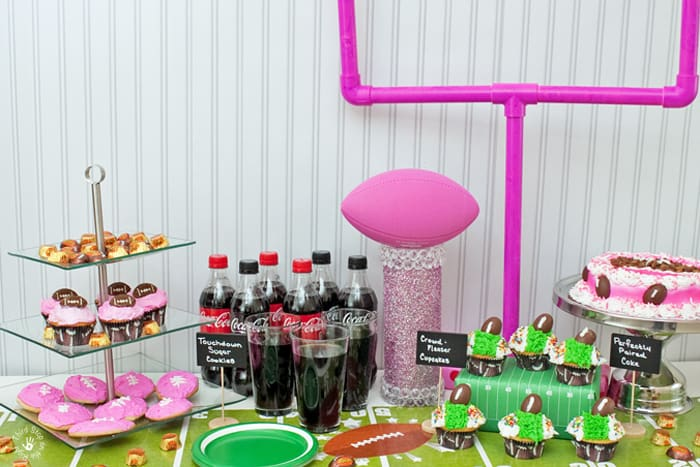 Complete pink football party tablescape including goal post, trophy, cookie tier, and cake.