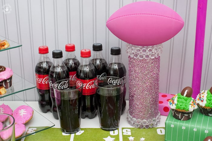 A pink football trophy made from a tall glass vase and decorated with glass gems, glitter, and has a pink football placed on top.