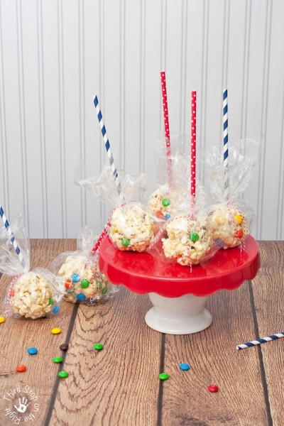 Four popcorn balls on red cake plate and two additional popcorn balls sitting on the table.