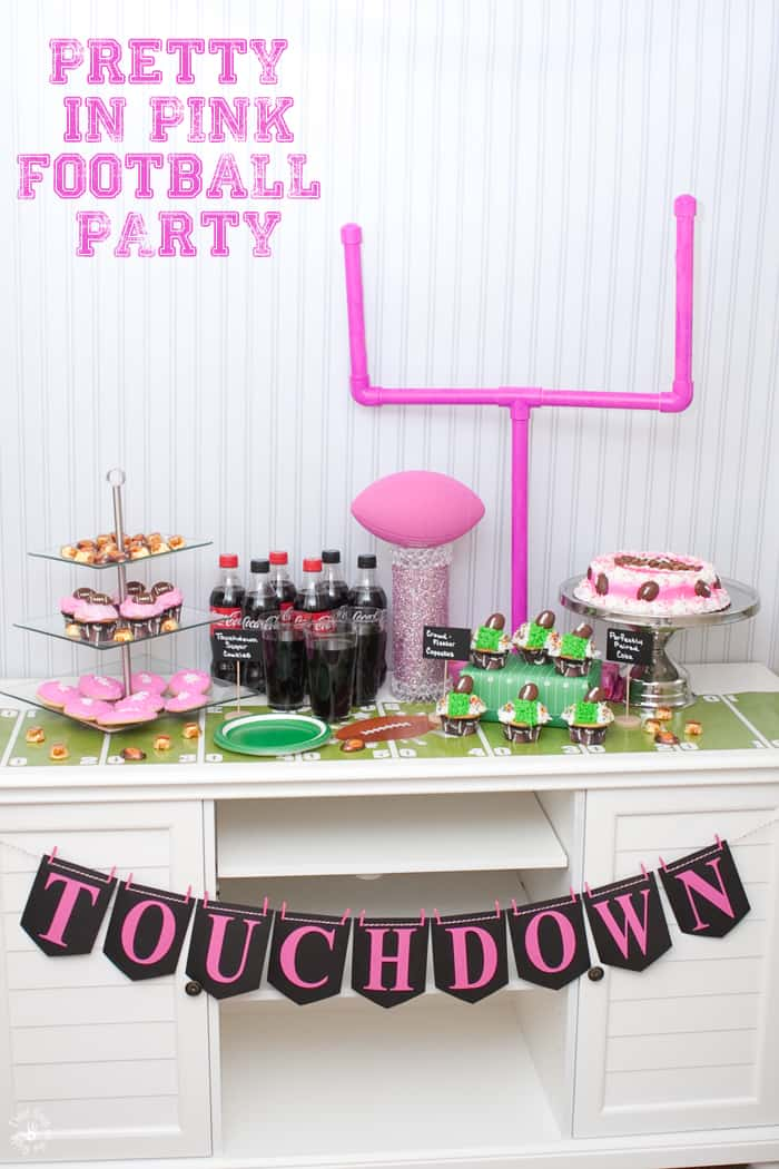 A pink football spread including a pink goal post, cupcakes, a cake tier, and even a pink sparkly football trophy.