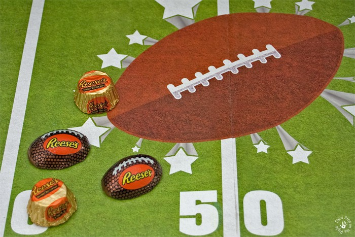 Traditional REESE'S Peanut Butter Cups and REESE's peanut butter cups in a football shape on a football field table runner.