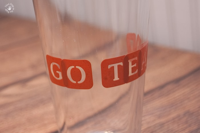 Alphabet stencils on drinking glass.