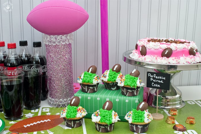 Cupcakes which are decorated to look like a football stadium as well as a pink cake and a football trophy sit on the table.