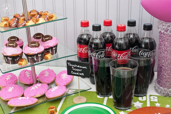 Coca-Cola bottles, pink glitter football trophy, and cookie tier with cookies, candy and cupcakes on a table.