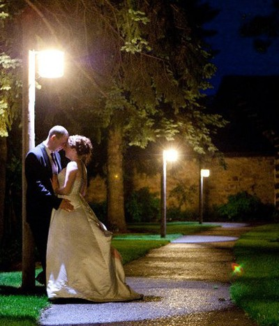 A newly married couple is kissing under a street lamp.
