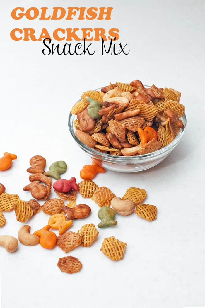 Goldfish® crackers, cereal, pretzels, and cashew snack mix in a clear bowl on a white countertop.
