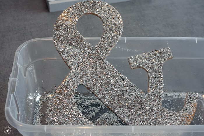Wooden ampersand with silver glitter covering it.