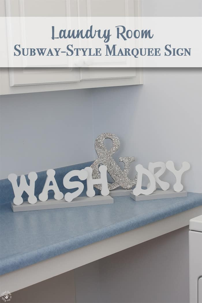 White letters spelling out WASH and DRY on a blue countertop with white cabinets