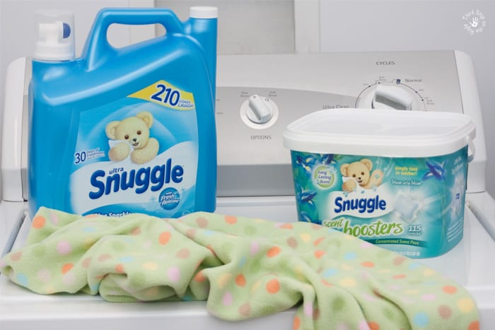 Snuggle Ultra fabric conditioner and Snuggle Scent Boosters on washing machine with a child's blanket.