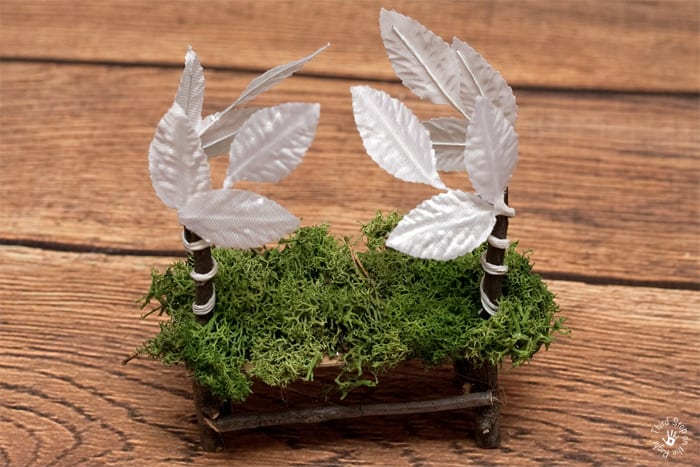 Fairy bed covered in moss and embellished with white leaves