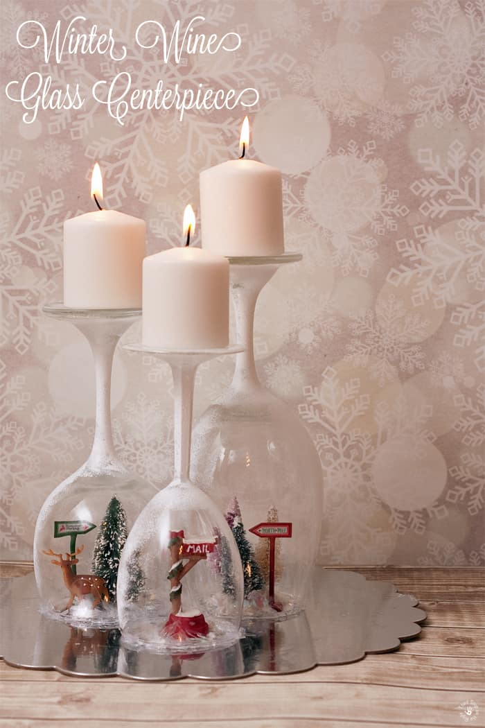 This beautiful Winter Wine Glass Centerpiece is a unique addition to a holiday table, mantle, or even bookcase. Plus, it uses materials that you can get from the Dollar Store!