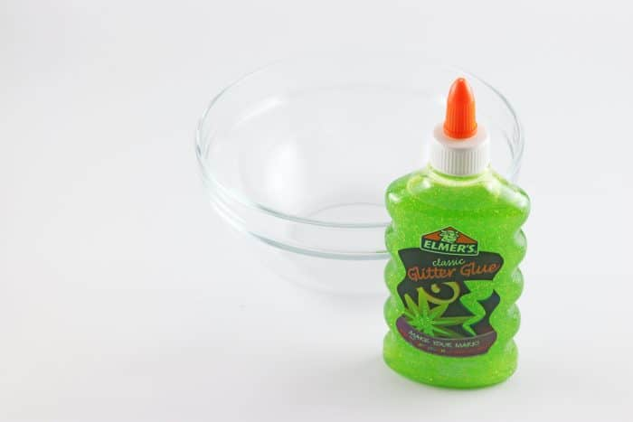 Bottle of Green Glitter glue and a glass mixing bowl ready to make slime.