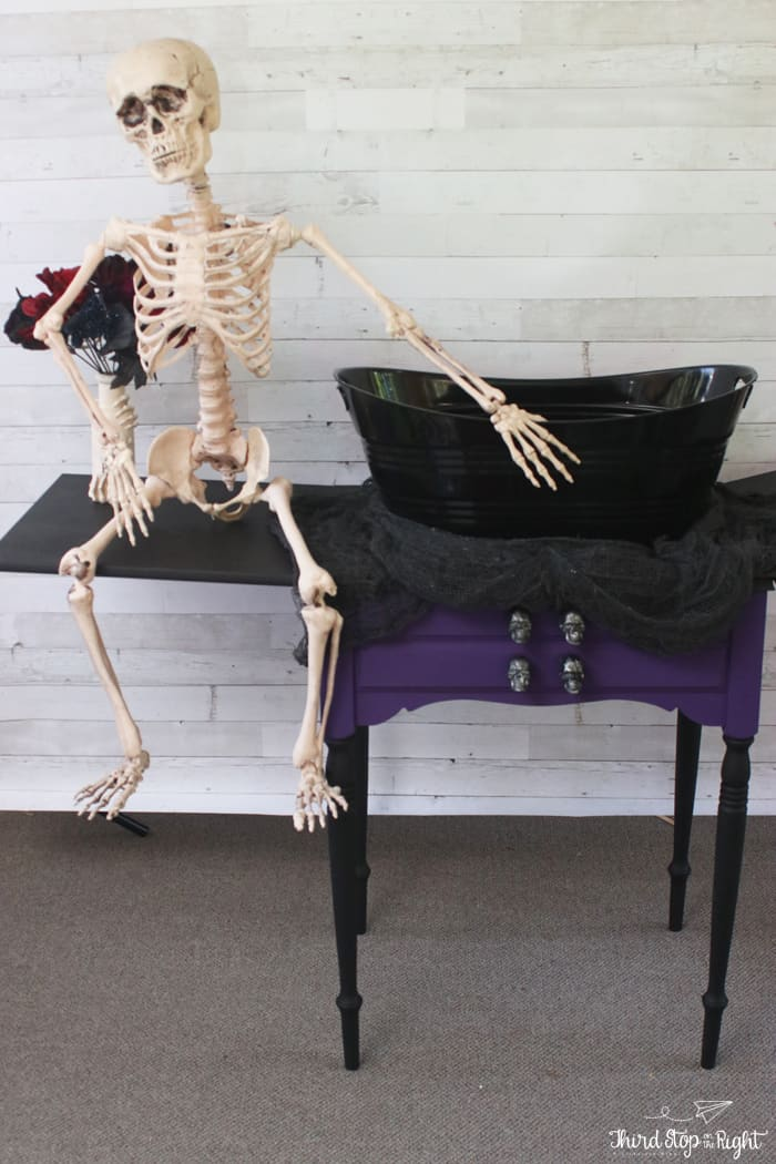 Skeleton sitting with candy bowl